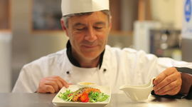 Smiling Chef Pouring Dressing Over Salmon And Salad Dish And Presenting Royalty-free stock video